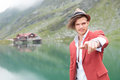 Young casual man pointing his finger near lake to you while standing a in the mountains Stock Photography
