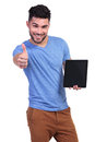 Young casual man recommending a tablet pad or the news he reads on it Royalty Free Stock Image