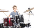 Young caucasian boy plays drums in studio against white backgrou Royalty Free Stock Photo