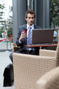 Young caucasian businessman using his laptop in cafe drinking Stock Photography
