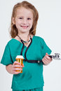 Young caucasian girl dressed up playing doctor wearing green surgery outfit stethoscope holding pill bottle Stock Image