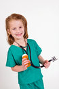 Young caucasian girl dressed up playing doctor wearing green surgery outfit stethoscope holding pill bottle Royalty Free Stock Photo