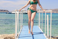 Young Caucasian girl in a green swimsuit on the blue pier, by background blue Ionian sea, Balos, Greece Royalty Free Stock Photo