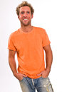 Young caucasian male in a bright orange t shirt and jeans blonde with blue eyes Stock Image