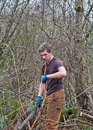 Young Man Clearing Bush with Machete Royalty Free Stock Photo
