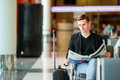 Young caucasian man with newspaper at the airport while waiting for boarding. Casual young businessman wearing suit Royalty Free Stock Photo