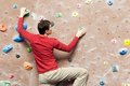 Young caucasian man rock climbing indoors Royalty Free Stock Photo