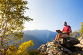 Young caucasian man sitting outdoor on a rock working on a lapto Royalty Free Stock Photo
