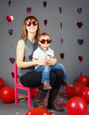 Young Caucasian mother sitting on small pink chair with baby boy toddler on her laps knees in studio wearing funny glasses Royalty Free Stock Photo