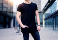 Young caucasian muscular man wearing black tshirt and jeans posing on the street of the modern city. Blurred background Royalty Free Stock Photo