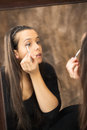 Young caucasian woman applying eye shadow mirror reflection of a Stock Image