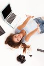 Young caucasian woman with electronic devices lying on a white floor Stock Photography