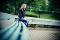 Young caucasian woman sitting alone on a bench in depression. Royalty Free Stock Photo