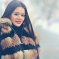 Young caucasian woman in warm fur coat outdoors Royalty Free Stock Photography