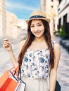 Young charming asian woman holding shopping bags on the street Royalty Free Stock Photo