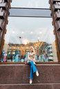 Young charming blonde model with trendy look posing while sitting on a shop sill against big window with copy space, Royalty Free Stock Photo