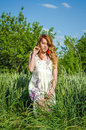 Young charming girl in a white sundress beautiful, sexy walking in the field among the wheat spikelets with flower red poppies in Royalty Free Stock Photo