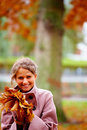 Young charming lady holding maple leaves Royalty Free Stock Image