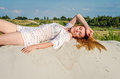 Young charming sexy girl with long hair and make-up in bikini bathing suit, in an erotic pose lying and sunning on a sunny hot day Royalty Free Stock Photo