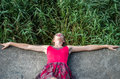Young charming slim sexy young blonde woman lying in erotic pose on the gray concrete steps in a red dress and boots in an abandon Royalty Free Stock Photo