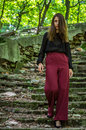 Young charming teenager girl with long dark hair is a graceful gait destroyed by an ancient staircase the steps in striysky park i Royalty Free Stock Photography