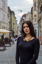Young charming woman with long curly hair, strolling among the old town of Lviv architecture in sexy black dress Royalty Free Stock Photo