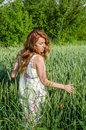 Young charming woman walking outdoors in a field near the green bushes and trees, hand patting wheat ears, dressed in a beautiful Royalty Free Stock Photo