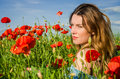 A young cheerful beautiful girl walks in a poppy meadow among red blooming poppies on a bright, hot, sunny summer day Royalty Free Stock Photo