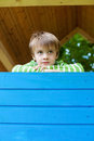 Young cheerful boy inside a blue playhouse looking at something the Stock Photos