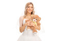 Young cheerful bride holding a teddy bear and looking at the camera isolated on white background Royalty Free Stock Photos