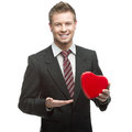 Young smiling businessman holding big red heart