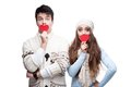 Young cheerful casual couple holding red hearts Royalty Free Stock Photos