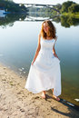 Young cheerful girl bride walk barefoot the sunny coast of the river in a white dress outdoor Royalty Free Stock Images