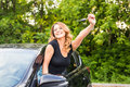 Young cheerful joyful smiling gorgeous woman holding up keys to her first new car. Customer satisfaction Royalty Free Stock Photo