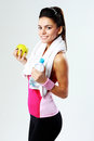 Young cheerful sport woman with apple and bottle of water on gray background Stock Image