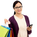 Young cheerful woman holding shopping bags and mobile phone Royalty Free Stock Photos
