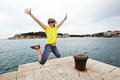 Young cheerful woman jumping on the pier near sea Stock Image