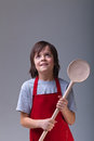 Young chef with apron and large wooden spoon looking up copy space Royalty Free Stock Image