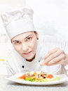 Young chef decorating delicious salad Royalty Free Stock Photography