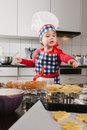 Young chef making cookies photo of an adorable boy in a hat and apron in the kitchen Stock Images