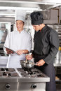 Young chefs with digital tablet preparing food male in restaurant kitchen Royalty Free Stock Photos