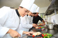 Young chefs preparing delicatessen team of dishes Stock Photos