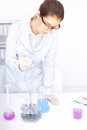Young chemical female researcher with vials and flasks Royalty Free Stock Images