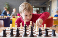Young chess player at a tournament child making move with horse during school with several other competitors in the background Royalty Free Stock Photography