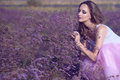 Young chic woman with artistic make up and long flying hair smelling violet flowers with closed eyes Royalty Free Stock Photo
