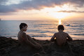 Young child boy and his friend or brother playing with sand at beach covering himself.Warm sunset light. Family summer Royalty Free Stock Photo