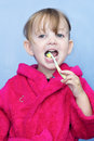 Young child cleaning teeth preschool girl her she s wearing a pink dressing gown against a blue background Stock Photos