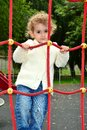 Young child climbing pretty girl having fun up a red rope ladder at a playground in the park Stock Image