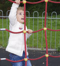 Young child climbing pretty girl having fun up a red rope ladder at a playground in the park Royalty Free Stock Images