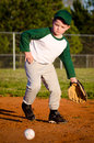 Young child fielding ball while playing baseball Stock Image